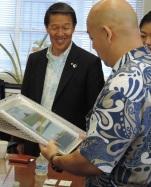 "Chair Ernest Martin views a gift with Chigasaki Council Chair Tadao Hirose depicting Chigasaki's Eboshi-Iwa, which bears similarities to Mokolii Island, aka ""Chinaman's Hat""."