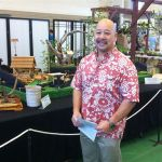 Council Chair Ernie Martin in front of a minature Japanese village.