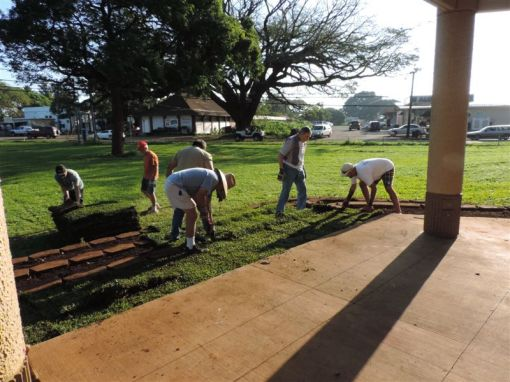 Volunteers hard at work installing the grass sod.