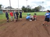 Volunteers re-installing the bases after fixing the field.