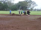 Volunteers at work shoveling dirt to even out the softball field.
