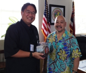 Brandon Mitsuda and Council Chair Ernie Martin with the money collected for Hawaii Food Bank.